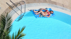 Pretty woman in swimsuit lies on air mattress in outdoor pool Stock Footage