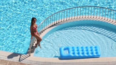 Cute girl in swimsuit sits on railing near outdoor pool Stock Footage