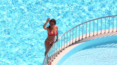 Cute girl in swimsuit waves by hand near railing of outdoor pool Stock Footage