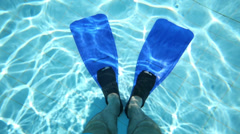 Male legs in blue flippers underwater in pure pool Stock Footage