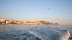 Glider flies over sea at summer evening near shore with hotels Stock Footage