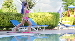 Young happy woman in swimsuit squats with dumbbell near pool Stock Footage