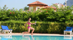Young happy woman squats with dumbbell near pool at sunny day Stock Footage
