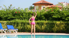 Back of young woman in swimsuit doing exercises with dumbbell Stock Footage