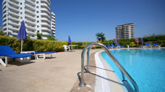 Railing for enter to pool and loungers near hotel Stock Footage