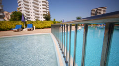 Metal railing in blue pool near hotel at sunny summer day Stock Footage