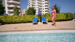 Young beautiful woman in swimsuit walks near blue pool and hotel Stock Footage