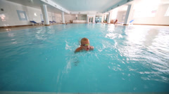 Boy swims crawl in pure indoor pool and somersaults in water Stock Footage