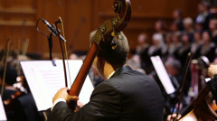 Violoncellist playing in the orchestra on stage conservatory Stock Footage