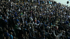 Thousand football fans, fan sector football game clapping sync Stock Footage