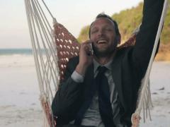 Businessman talking on cellphone, sit on hammock, exotic beach NTSC Stock Footage