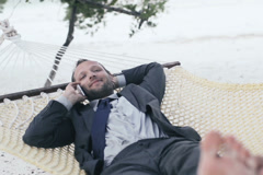 Businessman talking on cellphone, lying on hammock, exotic beach NTSC - stock footage