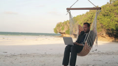Businessman with laptop sitting on hammock on tropical beach HD - stock footage