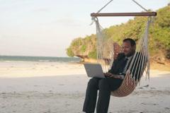 Businessman with laptop sitting on hammock on tropical beach NTSC Stock Footage