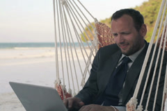 Businessman with laptop sitting on hammock on tropical beach NTSC - stock footage