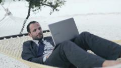Businessman working on laptop, lying on hammock on tropical beach HD Stock Footage