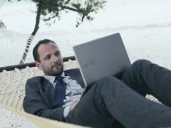 Businessman working on laptop, lying on hammock on tropical beach NTSC - stock footage