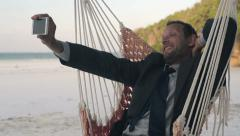 Businessman taking selfie with cellphone on hammock, tropical beach HD - stock footage