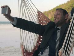 Businessman taking selfie with cellphone on hammock, tropical beach NTSC - stock footage