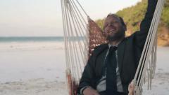 Happy businessman having fun on hammock on beautiful exotic beach HD Stock Footage