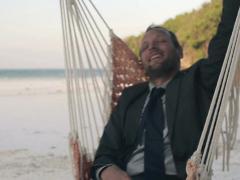 Happy businessman having fun on hammock on beautiful exotic beach NTSC Stock Footage