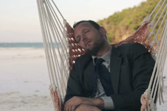 Young businessman sleeping on hammock on exotic beach NTSC - stock footage