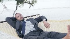 Young businessman sleeping on hammock on exotic beach HD Stock Footage