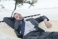 Young businessman sleeping on hammock on exotic beach NTSC Stock Footage