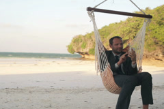 Businessman using smartphone, sitting on hammock on exotic beach NTSC Stock Footage