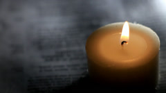 Reading a book, possibly the Bible, next to a candle Stock Footage