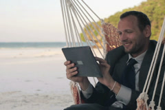 Businessman with tablet computer, sitting on hammock on exotic beach NTSC - stock footage