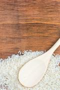 spoon and white rice grains on a wooden background - stock photo