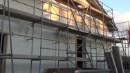 Stock Video Footage of Construction site of private home pan over scaffold