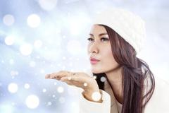 Beautiful lady blowing snowflakes on blue defocused lights Stock Illustration