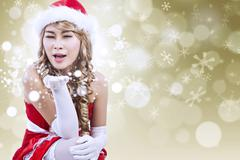 Sexy santa blowing snow in golden lights background Stock Illustration
