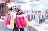 Stock Photo of shopaholic friends holding bags in the mall