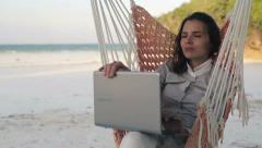 Businesswoman with laptop relaxing on hammock, on exotic beach HD - stock footage