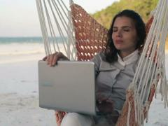 Businesswoman with laptop relaxing on hammock, on exotic beach NTSC Stock Footage