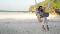 Businesswoman working on laptop on hammock, on exotic beach HD Stock Footage