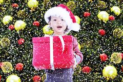 Stock Photo of happy girl receive christmas gift under tree