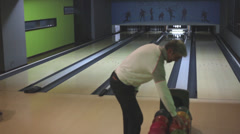 A man throwing a bowling ball in a bowling recreational center - stock footage