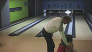 A man throwing a bowling ball in a bowling recreational center Stock Footage
