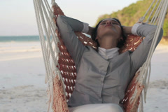 Happy businesswoman relaxing on hammock on exotic beach NTSC Stock Footage