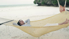 Happy businesswoman relaxing on hammock on exotic beach HD Stock Footage