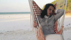 Young businesswoman sleeping on hammock on exotic beach HD - stock footage