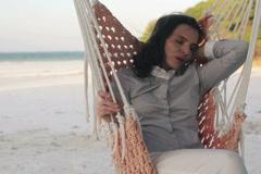 Young businesswoman sleeping on hammock on exotic beach NTSC - stock footage