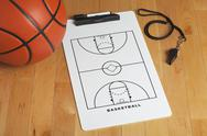 Stock Photo of a basketball with coach's clipboard and whistle on a wooden gymnasium floor