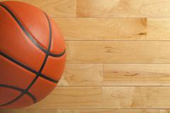 basketball on wood gym floor viewed from above - stock photo