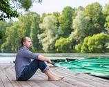 Stock Photo of young handsome bearded man sitting on wooden pier in summer day, meditating
