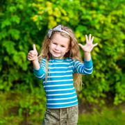 Cute blond little girl with long curly hair showing six fingers (her age)  Stock Photos